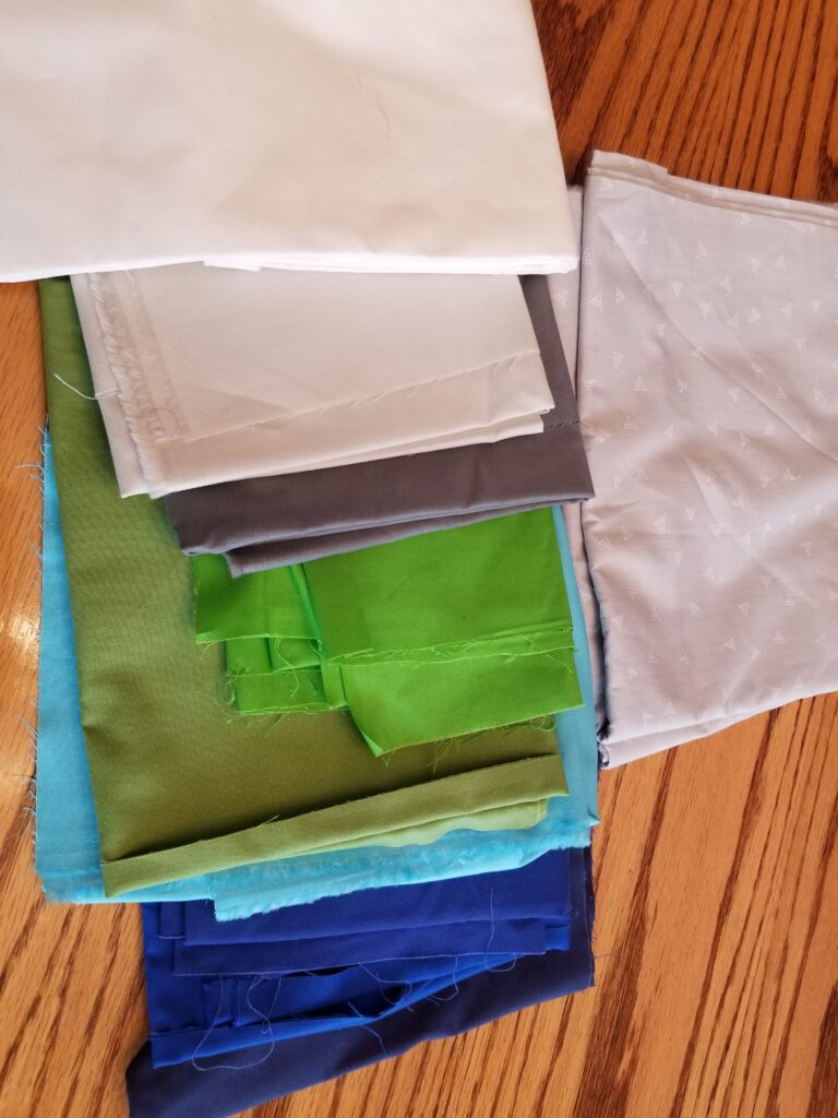 entropy quilt, fabric selection in blue, green, and gray